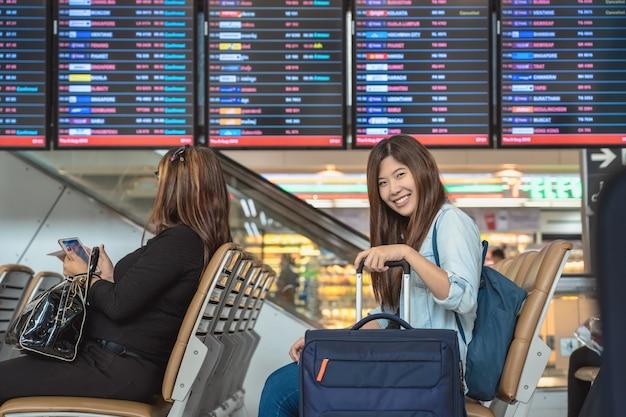 Voyageur asiatique avec des bagages avec passeport assis sur la planche de vol pour l'enregistrement Photo Premium