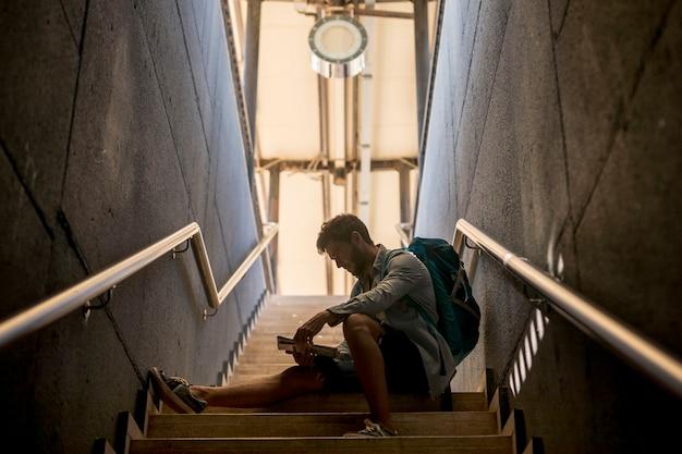 Voyageur assis dans les escaliers de la gare Photo gratuit