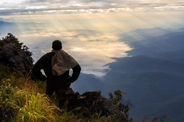 Un voyageur au sommet de la montagne, assis sur le rocher en regardant le lever du soleil Photo Premium