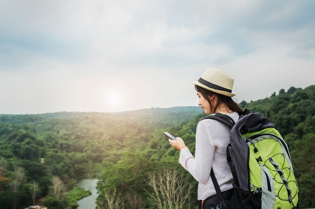 Voyageur de belle femme asiatique avec sac à dos se détendre en vacances sur la montagne avec l'aide de mobile Photo Premium