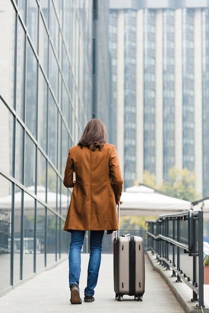 Voyageur de dos avec bagages Photo gratuit