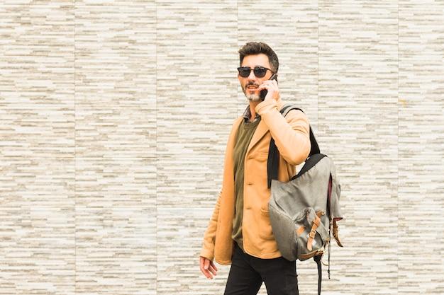 Voyageur élégant debout contre un mur parlant sur un téléphone mobile Photo gratuit