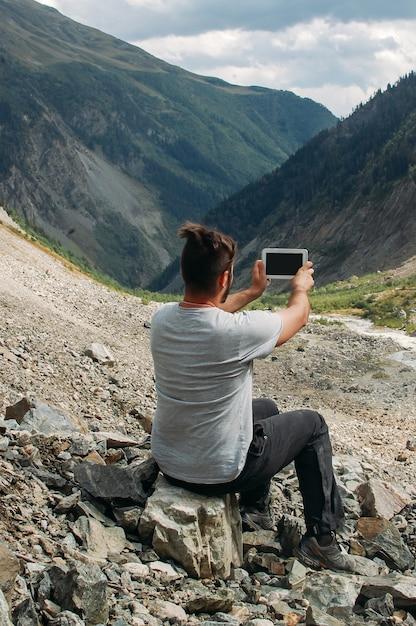 Voyageur Fait Une Photo Avec Sa Tablette Dans Les Montagnes Photo Premium