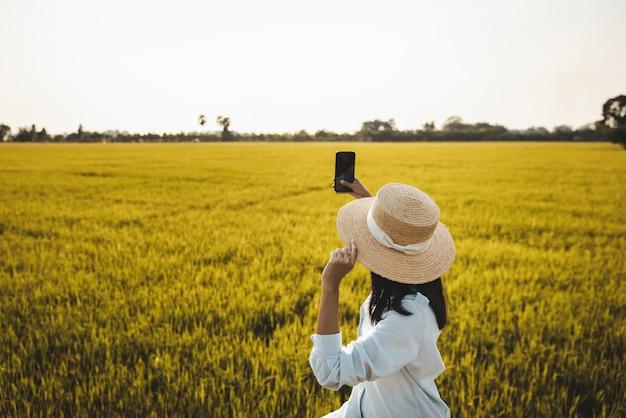 Voyageur Femme Asiatique à L'aide De Téléphone Mobile Sur Rizière En Ferme à Nakhon Nayok Thaïlande Photo Premium