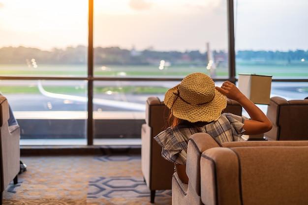 Voyageur de femme avec chapeau à la recherche d'avion dans le lever du soleil Photo Premium