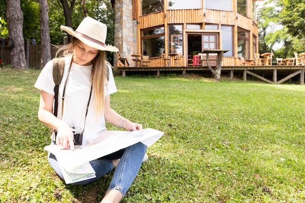 Voyageur sur l'herbe en regardant la carte Photo gratuit