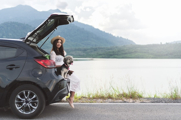 Voyageur heureuse jeune femme assise dans une voiture à hayon avec des chiens au lac et coucher de soleil. Photo Premium