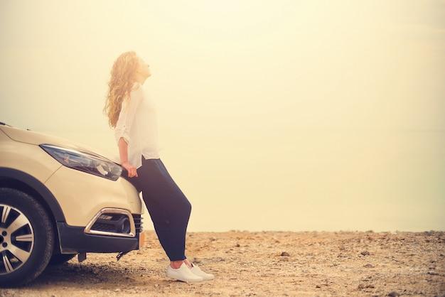 Voyageur heureux jeune femme élégante sur la route de la plage assis sur une voiture blanche multisegment Photo Premium