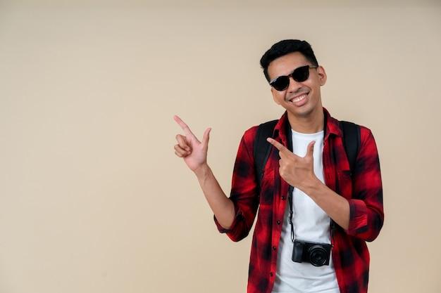 Voyageur hipster homme souriant et pointant sur fond de couleur crème Photo Premium