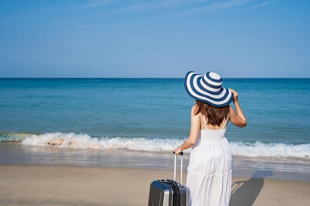 Voyageur De Jeune Femme Asiatique Avec Des Bagages à La Plage De Sable Tropicale Photo Premium