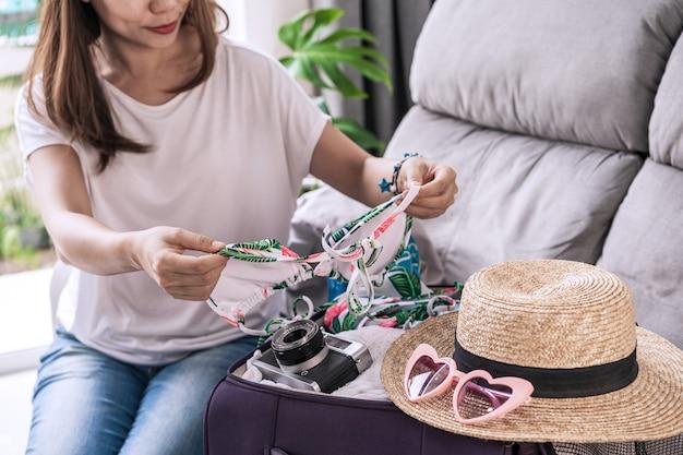 Voyageur De Jeune Femme Asiatique Emballant Sa Valise Et La Planification Des Vacances D'été Photo Premium