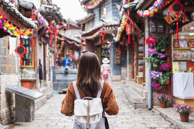 Voyageur de la jeune femme marchant dans la vieille ville de lijiang en chine, concept de mode de vie voyage Photo Premium