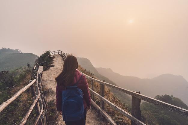 Voyageur jeune femme regardant le coucher de soleil sur la montagne Photo Premium