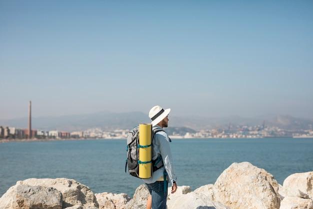 Voyageur latéral au bord de la mer Photo gratuit
