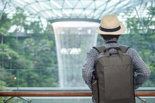Voyageur à la recherche d'un beau vortex de pluie à l'aéroport jewel changi Photo Premium