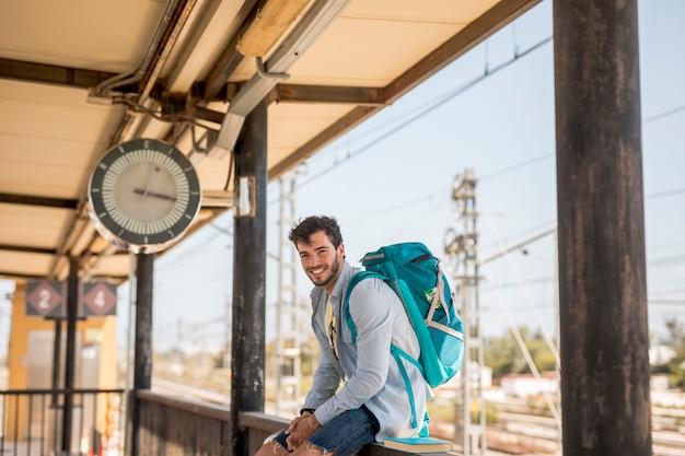 Voyageur souriant attendant le train Photo gratuit