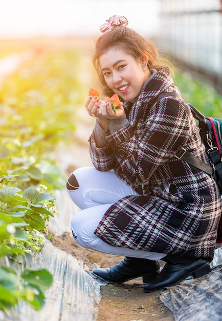 Voyageur thaïlandaises montrant une fraise rouge à la main dans l'agriculture des terres agricoles en corée Photo Premium