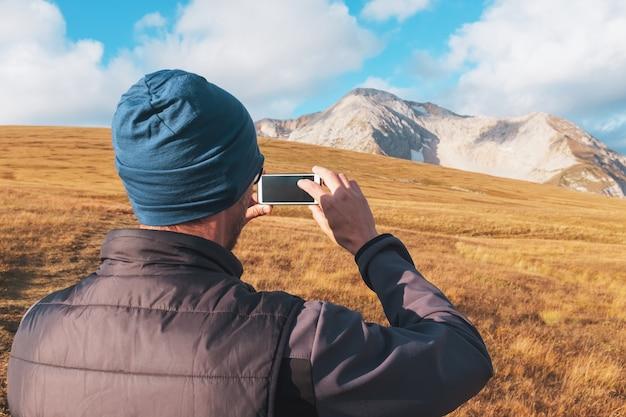 Un voyageur touristique photographie des montagnes couvertes de nuages sur un smartphone Photo Premium