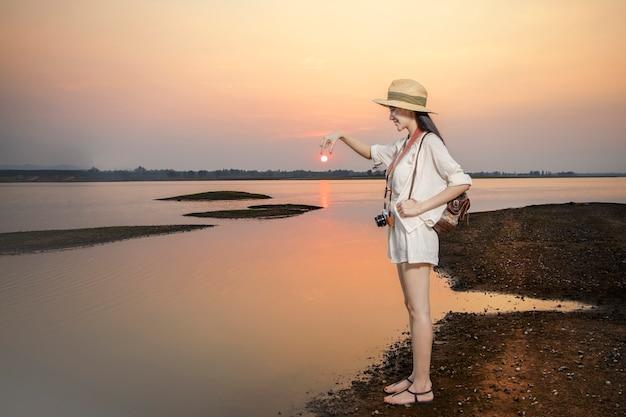 Les voyageurs portent des vêtements décontractés pour se détendre au coucher du soleil sur un lac tranquille Photo Premium
