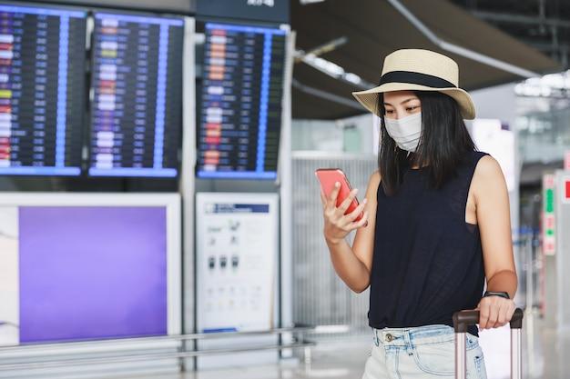 Voyagez Dans La Nouvelle Normalité Sous Le Concept De Virus Covid-19, Femme Asiatique Happy Traveler Avec Masque Et Bagages à L'aide D'un Téléphone Portable Et Asseyez-vous Sur Une Chaise De Distanciation Sociale Dans L'aéroport Du Terminal, Thaïlande Photo Premium