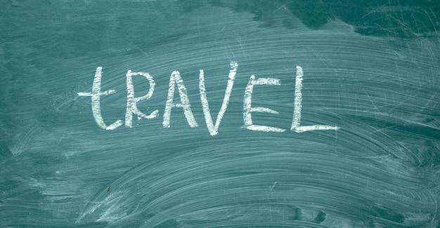 Voyagez à la main à la craie blanche sur un tableau vert. Photo Premium