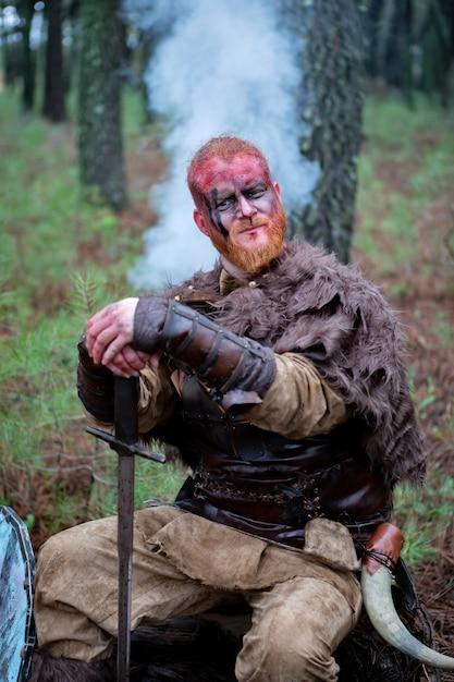 Vrai sanglant viking avec son épée de formation pour le combat Photo Premium