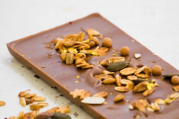 Une vue aérienne de l'avoine; graines et fruits secs sur tablette de chocolat Photo gratuit