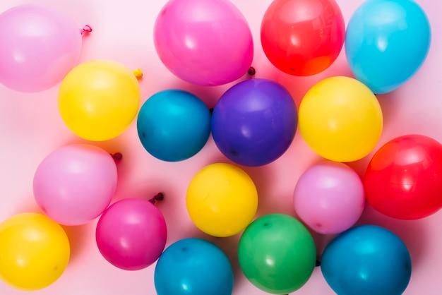 Une vue aérienne de ballons colorés gonflés sur fond rose Photo gratuit