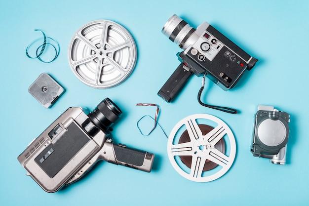 Une vue aérienne de bandes de film; bobine de film et divers type de caméscope sur fond bleu Photo gratuit