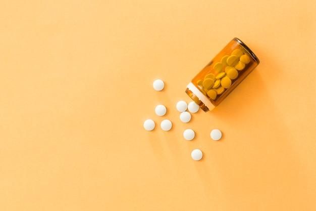 Vue Aérienne, De, Blanc, Pilules, Tomber, Depuis, Bouteille, Sur, Arrière-plan Coloré Photo gratuit