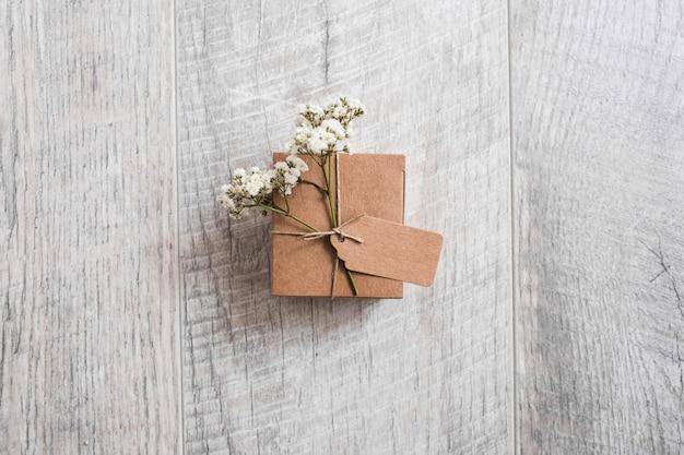 Vue aérienne d'une boîte en carton nouée avec une étiquette et des fleurs d'haleine de bébé sur un bureau en bois Photo gratuit