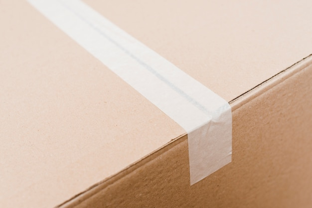 Vue aérienne d'une boîte en carton scellée avec du ruban d'emballage blanc Photo gratuit