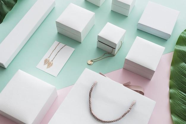Vue aérienne de boîtes blanches avec des bijoux en or sur fond de papier de couleur Photo gratuit