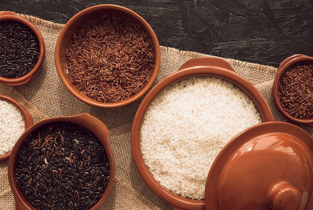 Vue aérienne de bols de riz non cuits sur une nappe de jute Photo gratuit