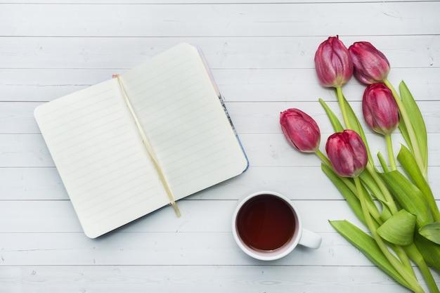 Vue aérienne d'un bouquet de tulipes et cahier et une tasse de café. Photo Premium