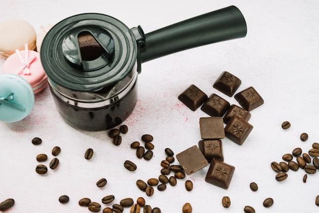 Vue aérienne d'une cafetière avec des morceaux de chocolat et des grains de café torréfiés Photo gratuit