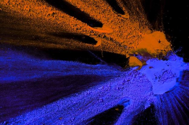 Vue aérienne de couleurs de poudre orange et bleu éclaboussés sur fond sombre Photo gratuit