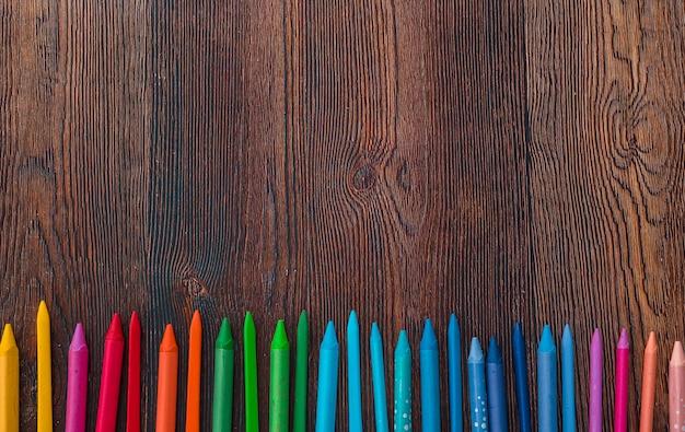 Vue aérienne de crayons de cire multicolores disposés en rangée au bas de l'arrière-plan Photo gratuit