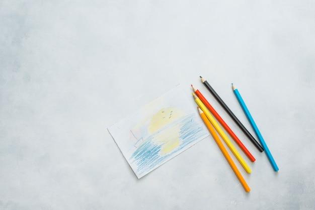 Vue aérienne de crayons de papier et de couleur dessinés sur fond blanc Photo gratuit