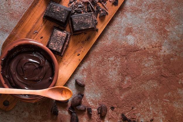 Vue aérienne de la crème au chocolat et des morceaux sur la table en désordre Photo gratuit