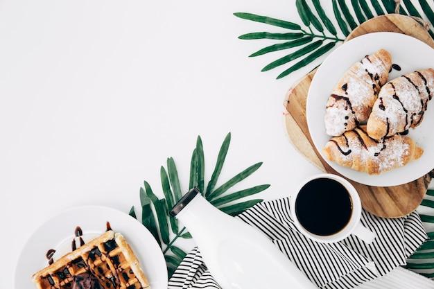 Une vue aérienne d'un croissant cuit au four; gaufres; bouteille; tasse à café sur les feuilles sur le fond blanc Photo gratuit