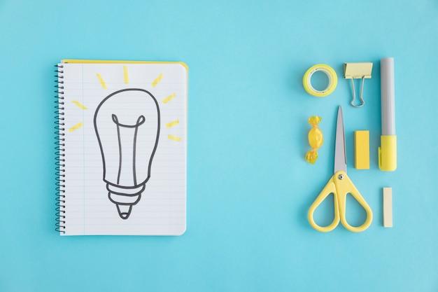 Vue aérienne, de, dessinés à la main, ampoule, sur, ordinateur portable, à, stationnaire, sur, arrière-plan bleu Photo gratuit