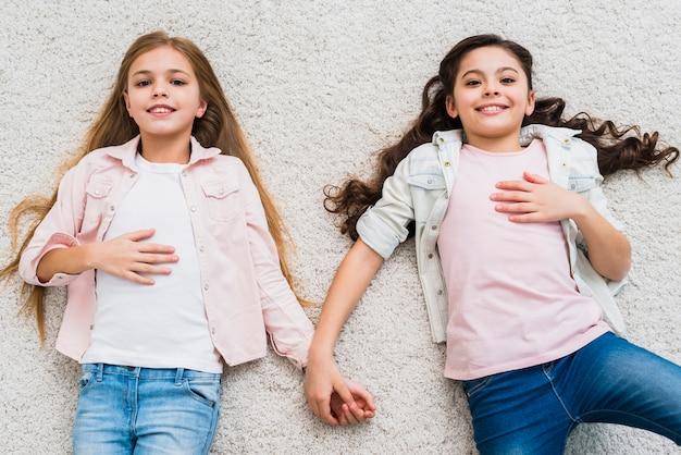 Une Vue Aérienne De Détendue Deux Filles Se Trouvant Sur Un Tapis En Levant Photo gratuit