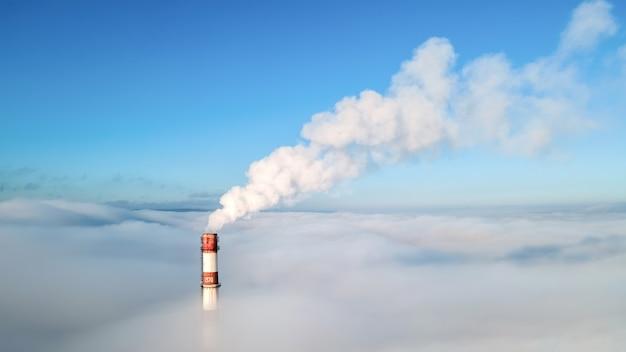 Vue Aérienne De Drone Du Tube De La Station Thermale Visible Au-dessus Des Nuages Avec De La Fumée Qui Sort. Ciel Bleu Et Clair Photo gratuit