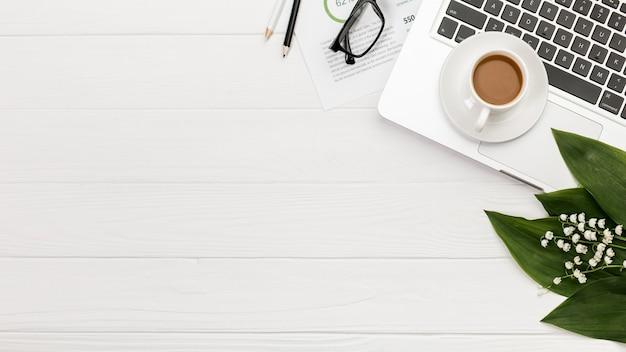 Vue aérienne du bloc-notes en spirale sur un ordinateur portable avec une tasse de café sur le bureau Photo gratuit