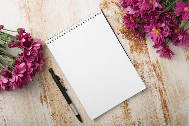 Vue aérienne du bloc-notes en spirale avec stylo et fleurs roses sur fond en bois Photo gratuit