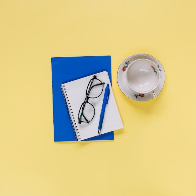 Vue aérienne du bloc-notes en spirale; tasse et lunettes sur la surface jaune Photo gratuit