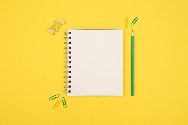 Vue aérienne du bloc-notes à spirale vierge avec un crayon et un trombone sur une surface jaune Photo gratuit