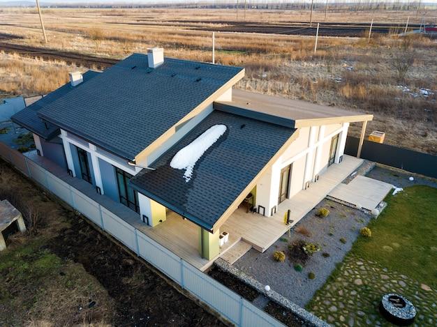 Vue aérienne du chalet de la maison d'habitation neuve et de la terrasse avec un toit en bardeaux sur une grande cour clôturée le jour d'hiver ensoleillé Photo Premium