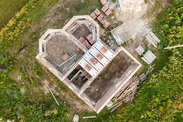 Vue aérienne du chantier de construction de la future maison, du sous-sol en brique et des piles de briques pour la construction. Photo Premium